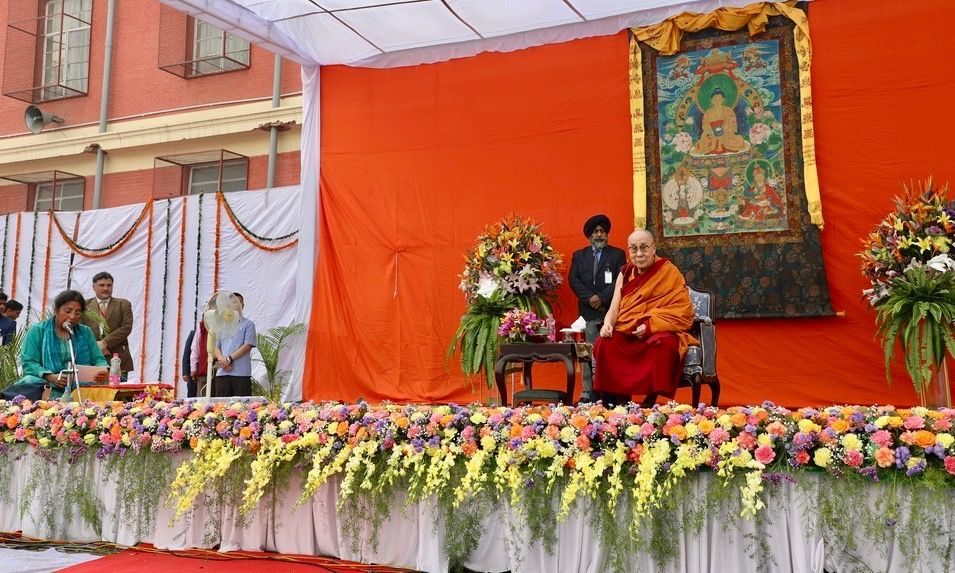 Doctor Renuka Singh dressed in turquoise blue seated on the stage speaking into a microphone while His Holiness the Dalai Lama is seated on a chair nearby on the stage smiling.