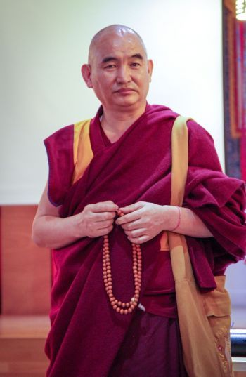 Geshe Dakpa Tsundue standing with a mala in his hands looking into the camera.
