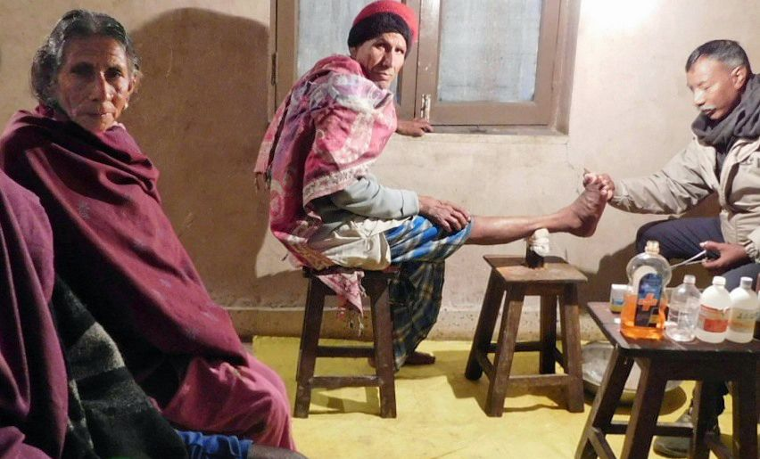 A person seated on a stool with leg extended receiving treatment for leprosy.