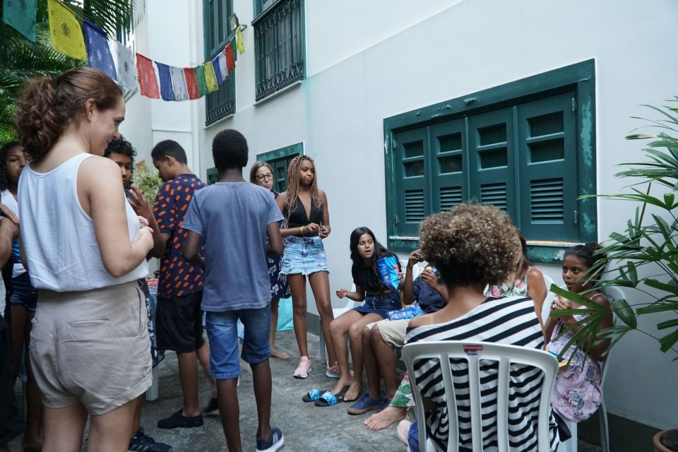Adults and teenagers standing and seated on chairs outside in the garden enjoying snacks and talking in small groups.