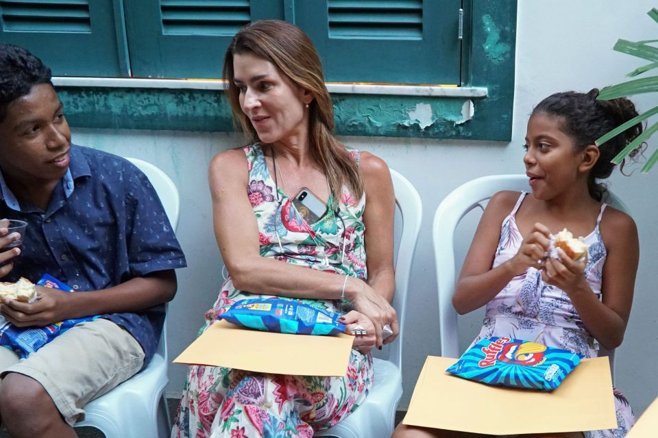 Daniela Vignoli wearing a flowered print dress seated between two teenagers enjoying snacks and conversation.