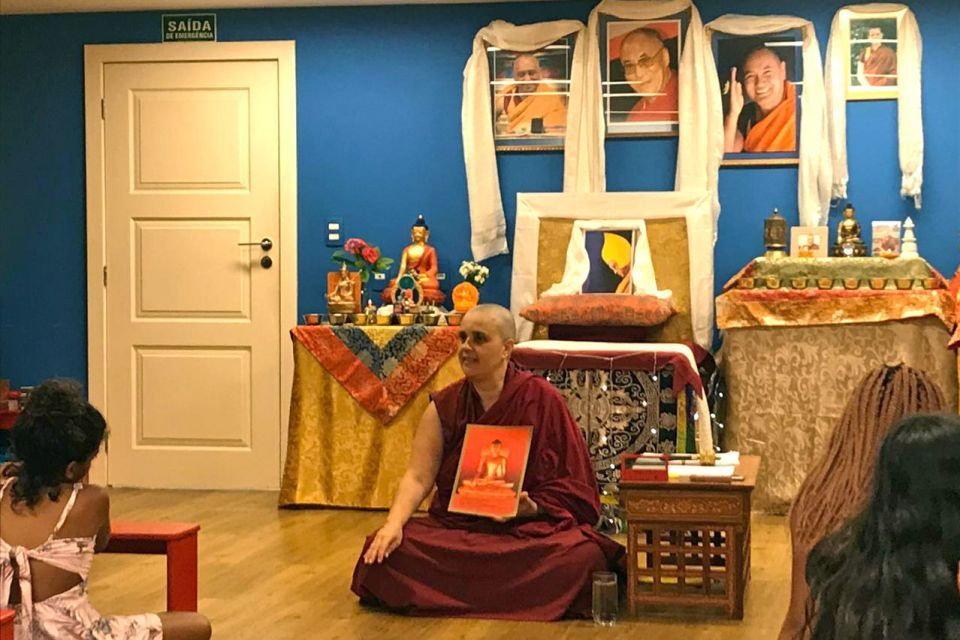 Venerable Tenzin Namdrol holding up a eight and a half by eleven inch picture of a golden Buddha on a red background for the audience to see.
