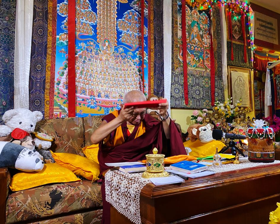lama zopa rinpoche holding a text to his forehead