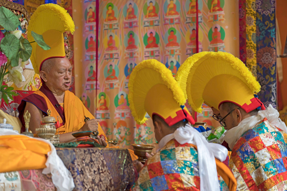 lama zopa rinpoche with three monks all wearing yellow ceremonial hats