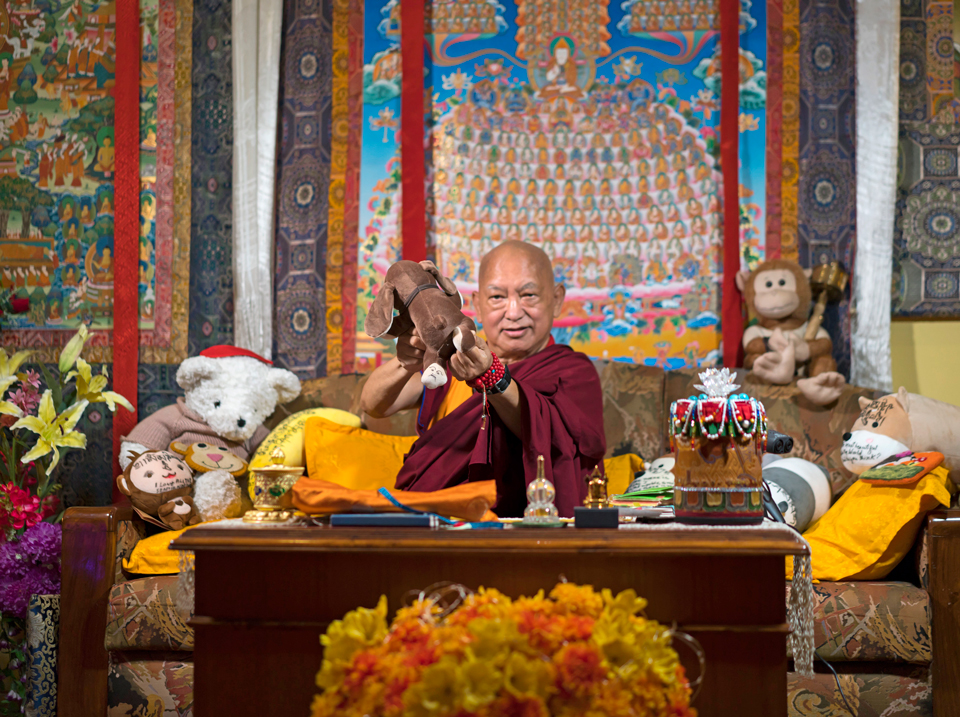 Lama Zopa Rinpoche showing the camera a plush toy