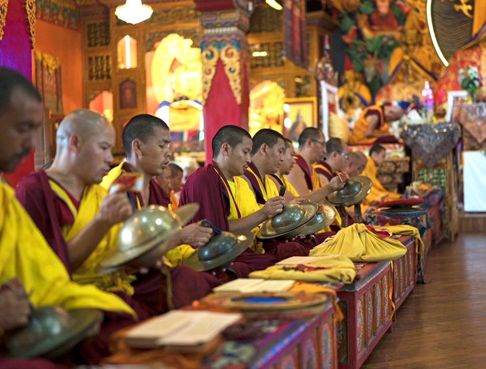 monks doing puja playing cymbals