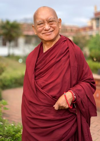 lama zopa rinpoche smiling in a garden