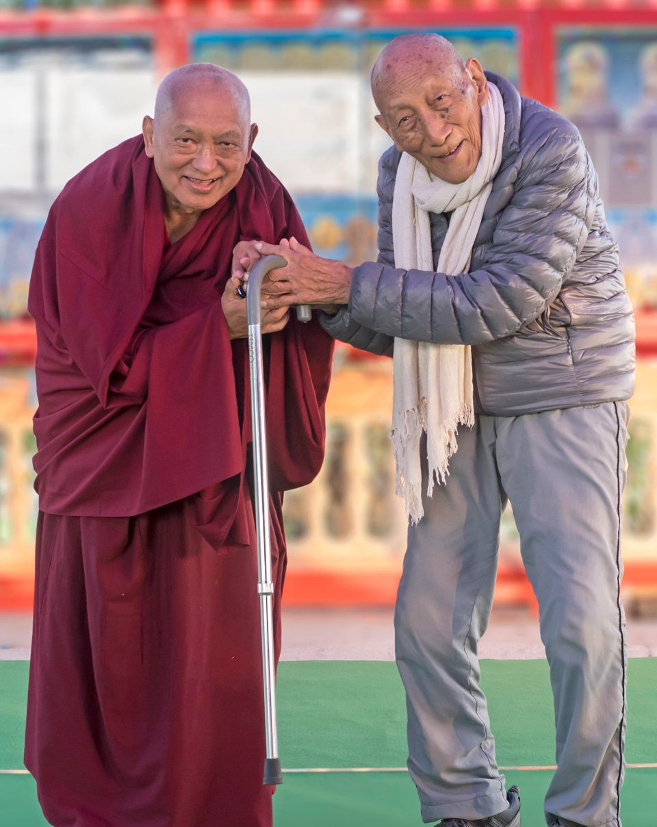lama zopa rinpoche and khyongla rato rinpoche standing and holding hands