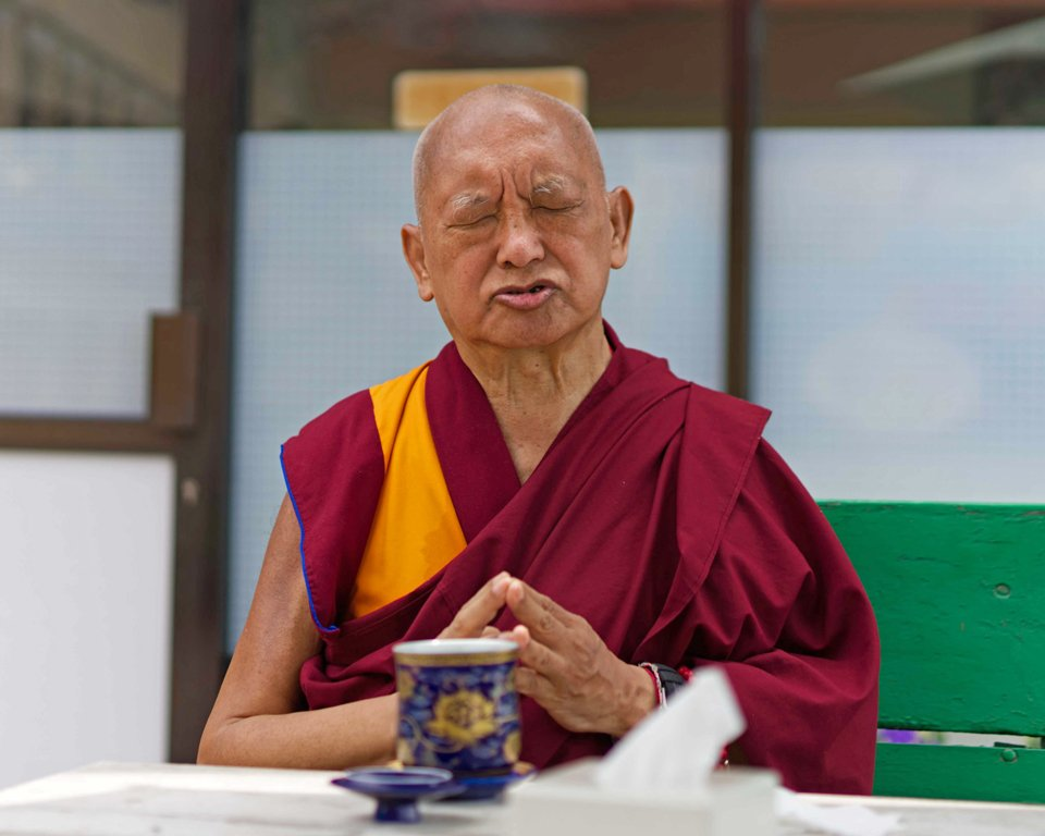 lama zopa rinpoche with closed eyes offering tea