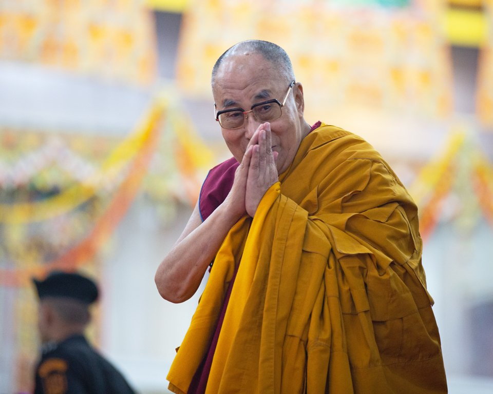 his holiness the dalai lama looking at camera with hands in prostration mudra