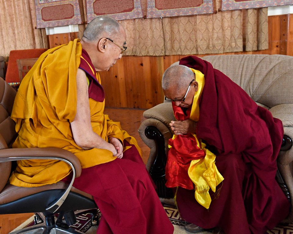 his holiness the dalai lama with lama zopa rinpoche bowing to him