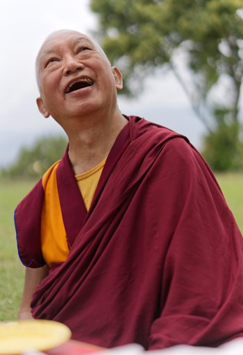 lama zopa rinpoche smiling and looking up at the sky