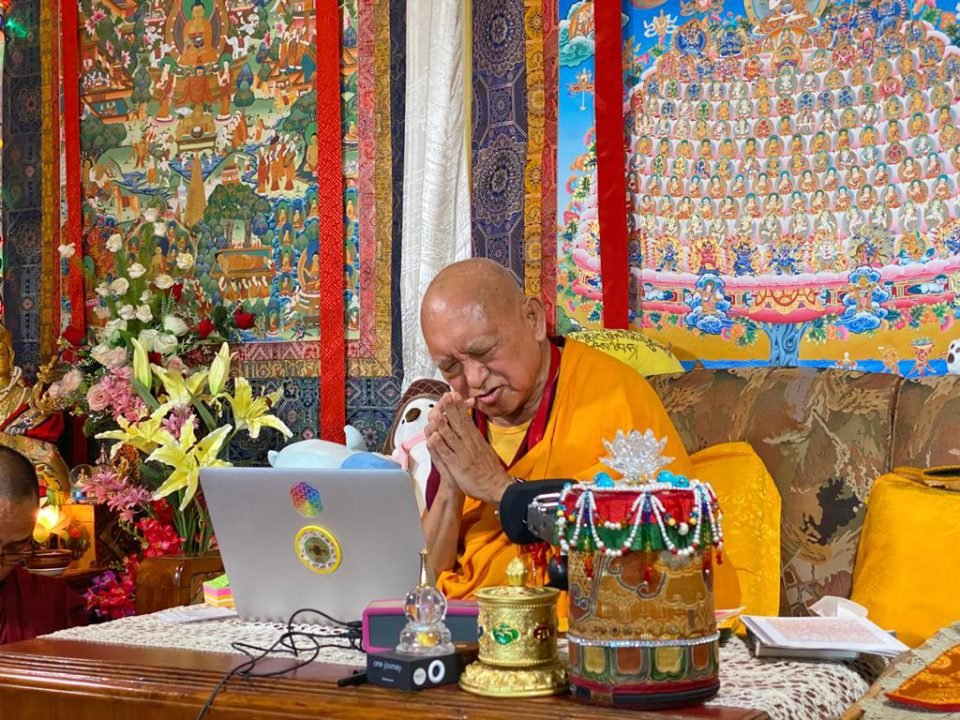rinpoche in front of a computer in his room with his hands in prostration mudra