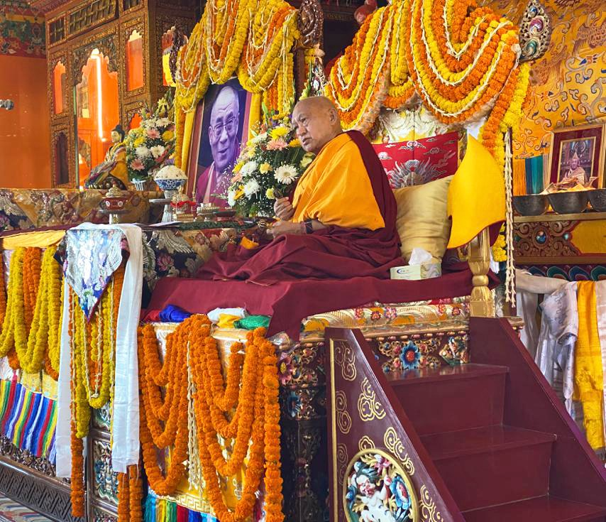 Lama Zopa Rinpoche on a throne decorated with marigold garlands