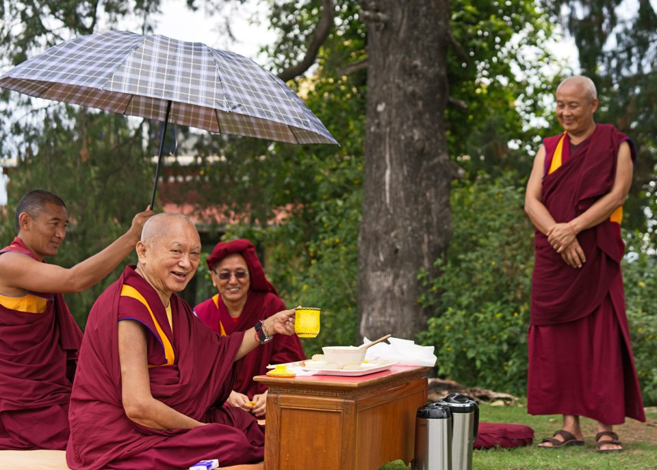 Lama Zopa Rinpoche holding up a tea mug sitting under tree