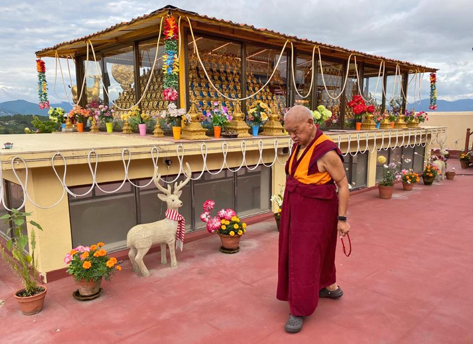 Lama Zopa Rinpoche walking with a mala in hand around 1,000 buddha statues