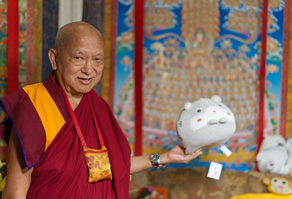 Lama Zopa Rinpoche holding up stuffed toy