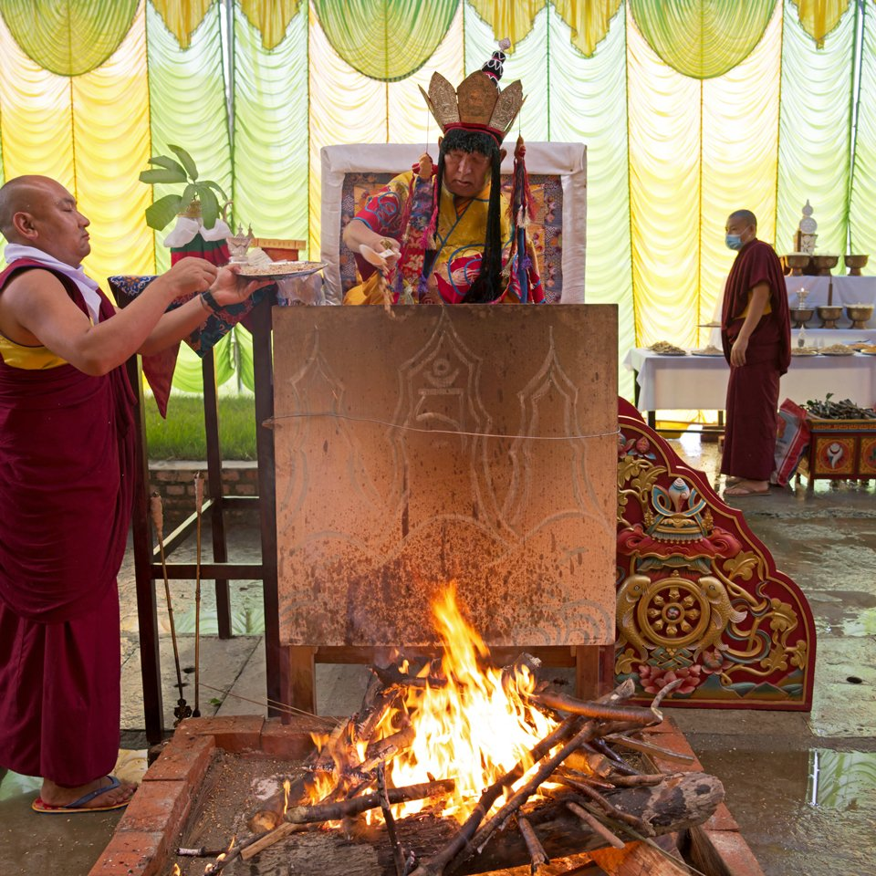 Lama Zopa Rinpoche wearing a ritual head piece and performing a fire puja