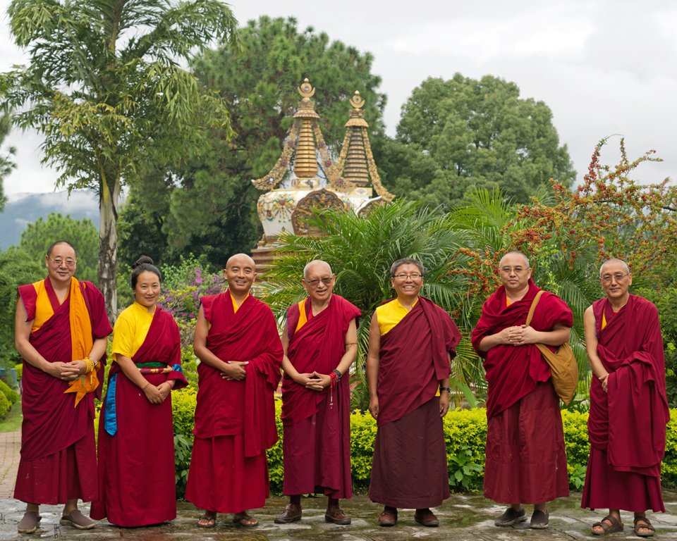 group of seven lamas standing in front of stupas in a garden