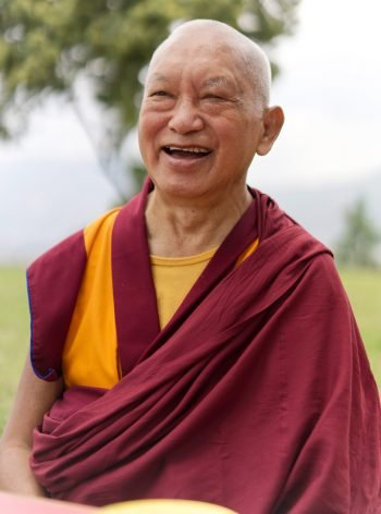 Lama Zopa Rinpoche smiling outside with a tree in the background