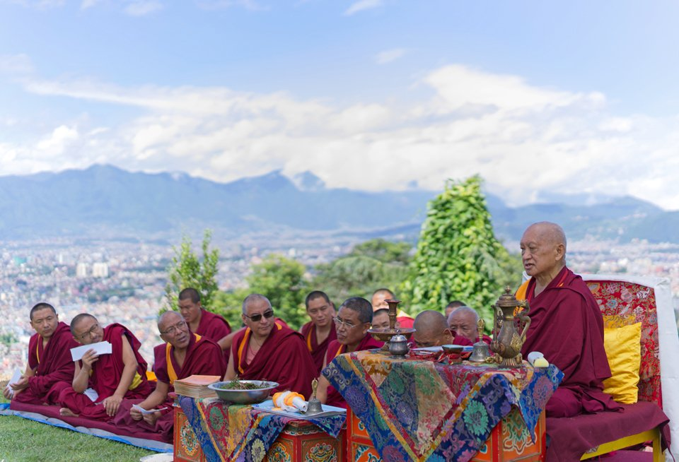 lama zopa rinpoche seated on throne and monks seated on the ground doing puja outside with mountains in the background