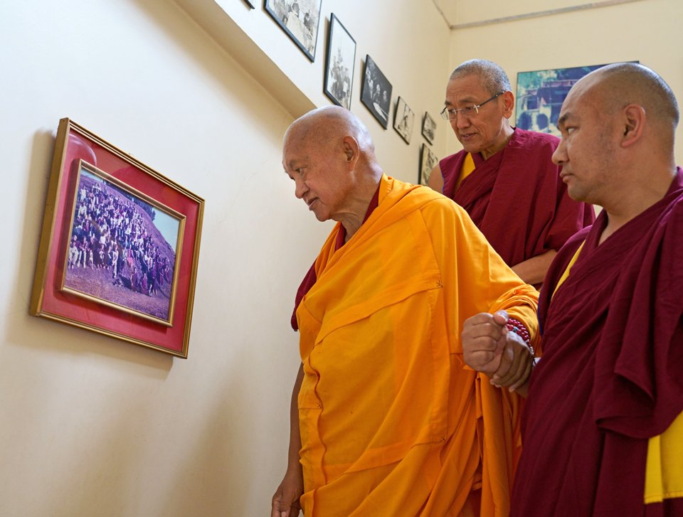 Lama Zopa Rinpoche pauses to look at a photo