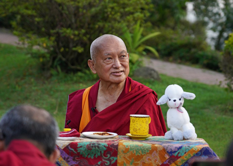 Lama Zopa Rinpoche sitting in garden with a tea cup and stuffed toy dog on his puja table