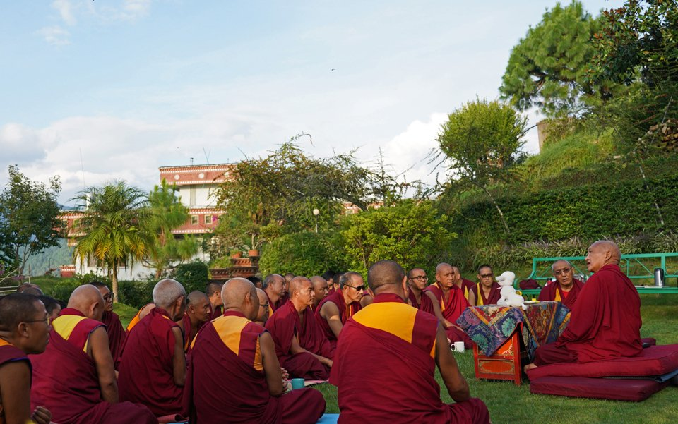 Lama Zopa Rinpoche sitting in garden with monks