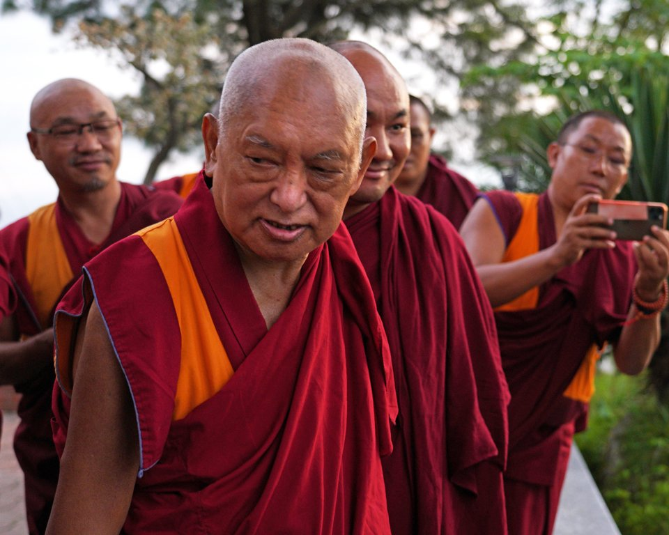 Lama Zopa Rinpoche walking with a group of monks