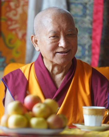 Lama Zopa Rinpoche smiling with a offering of apples and tea