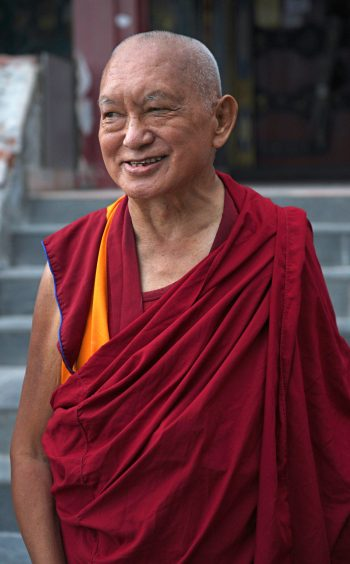 Lama Zopa Rinpoche smiling in front of the Kopan Gompa