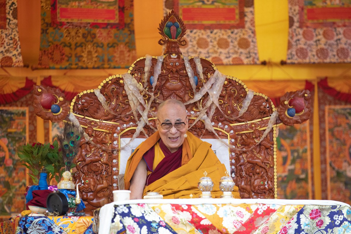His Holiness the Dalai Lama seated on a throne with an open smile on his face and the bottom of three thankgas visible behind him.