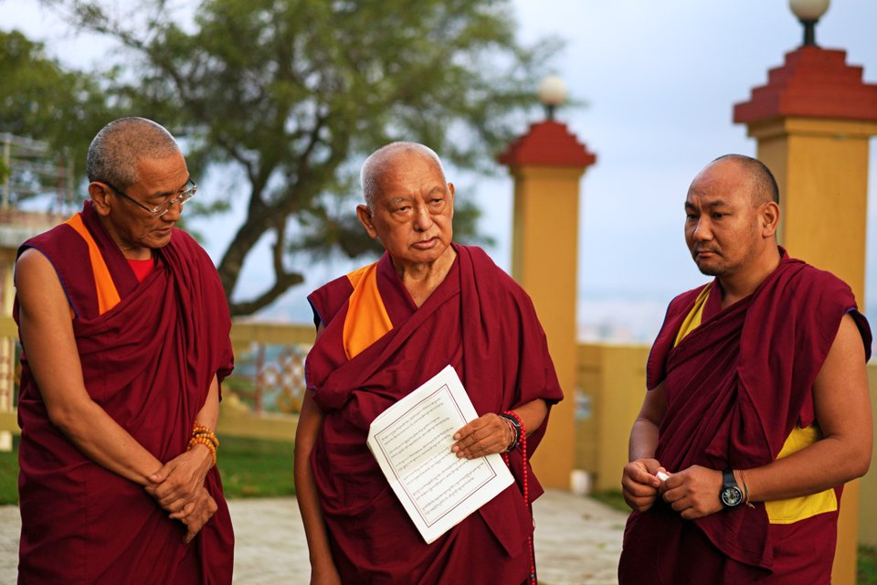 Khen Rinpoche Geshe Chonyi, Lama Zopa Rinpoche, and Ven. Thubten Tendar standing in the garden at Kopan Monastery