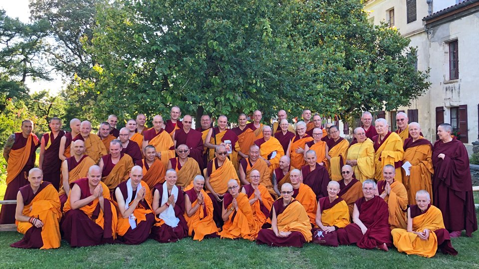 lama zopa rinpoche in a group photo with about forty sangha outside under a shade tree