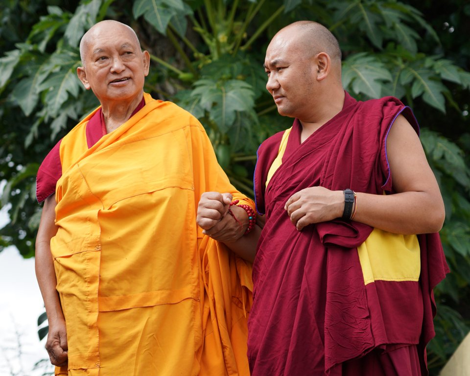 Lama Zopa Rinpoche walking with his attendant Ven. Tendar