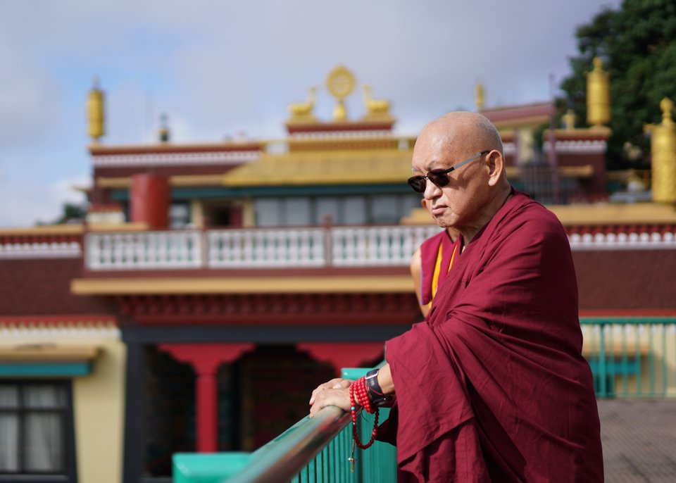 Lama Zopa Rinpoche looking out over a banister