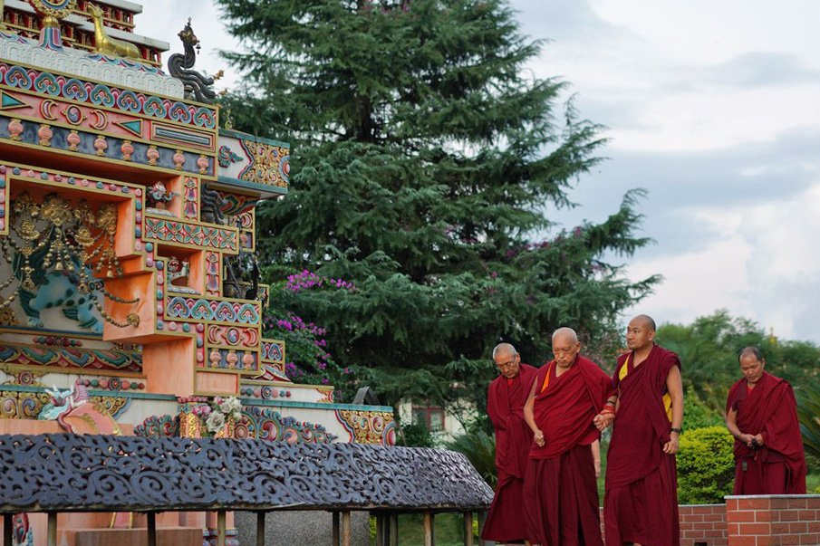 Lama Zopa Rinpoche with two monks walking around a very large and colorful stupa with a big green tree nearby.