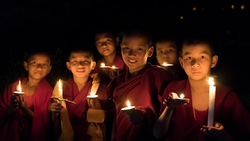 young monks holding candles and smiling