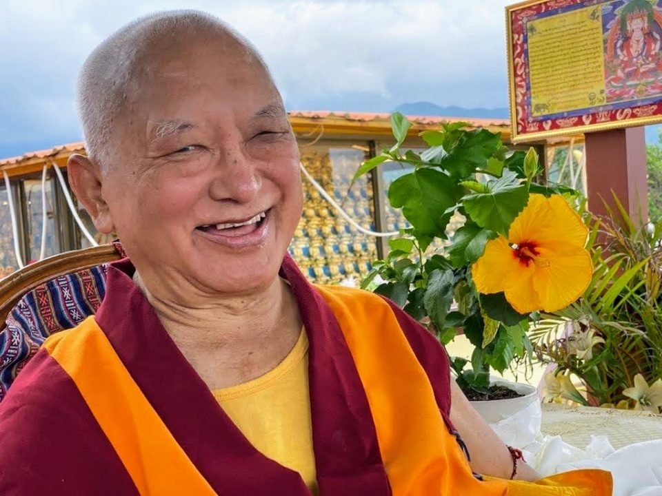 Lama Zopa Rinpoche smiling with flower next to him