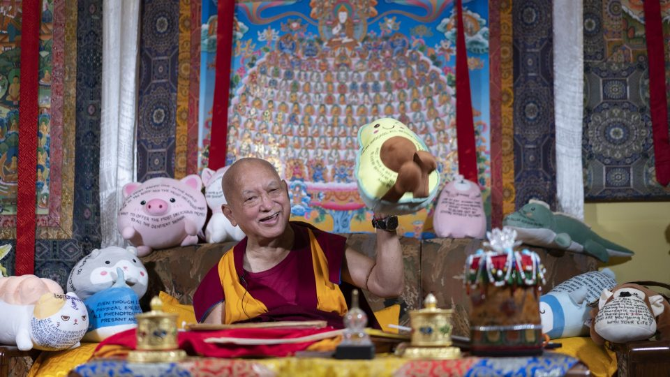 Lama Zopa Rinpoche holds up a stuffed plush avocado toy with a Dharma message written on it