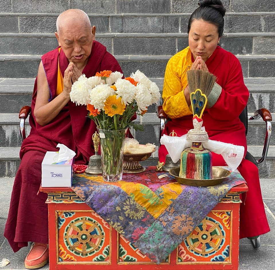 Lama Zopa Rinpoche and Khadro-la with hands in prostration mudra sitting behind a puja table full of offerings and ritual implements