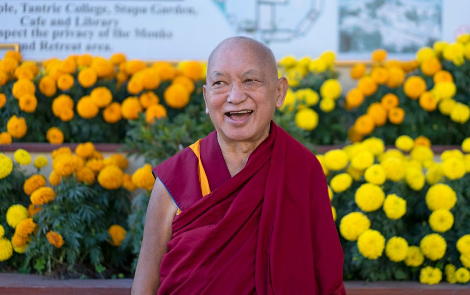 Lama Zopa Rinpoche standing in front of dozens of yellow and orange marigolds