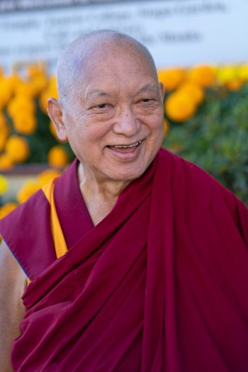 Lama Zopa Rinpoche smiling outside with blooming marigolds behind hime