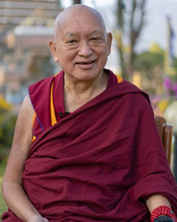 Lama Zopa Rinpoche smiling and sitting in the stupa garden at Kopan Monastery