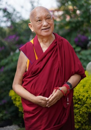 Lama Zopa Rinpoche smiling in a garden with green shrubs and purple blossoms behind him in the background