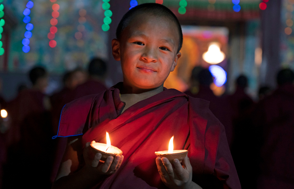 Young monk holds two lighted candles with other monks and light offering in the background