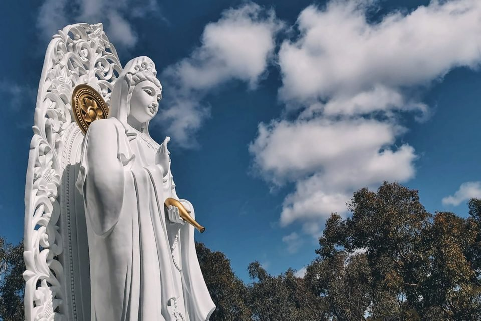 Tall white statue with intricate carving standing in front of trees and a blue sky with clouds.