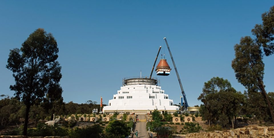 A crane lowering the spire onto the stupa.