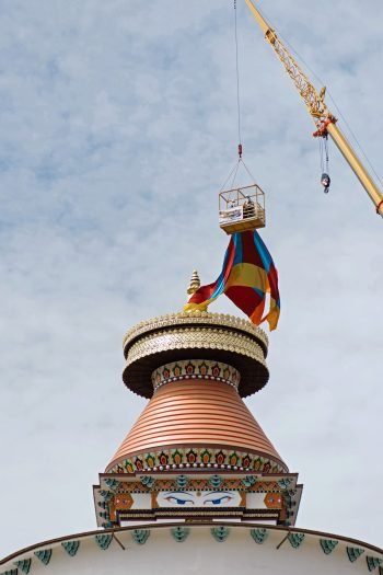 A close up of the spire being lowered onto the stupa by several people suspended in a cage above the stupa.