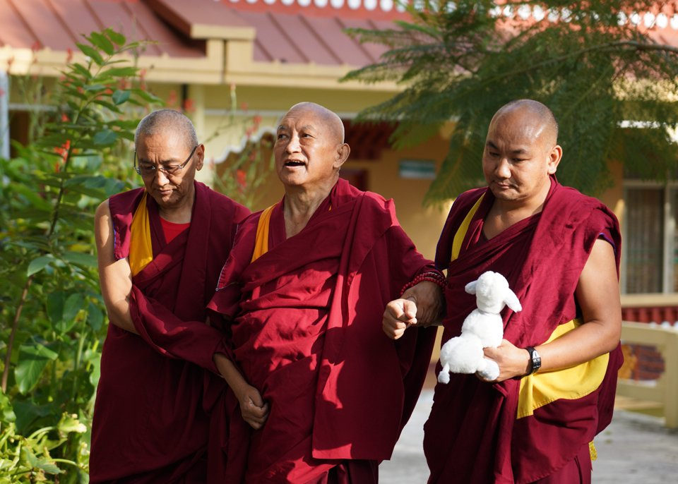 Lama Zopa Rinpoche walking with Khen Rinpoche and Ven Tendar, who is holding a stuffed toy